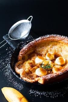 Concetto dell'alimento bambino olandese casalingo o pancake tedesco della guarnizione del caramello della banana in ghisa della padella sul nero