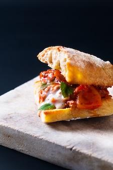 Concetto dell'alimento casalingo panino bolognese organico del pane dell'artigiano della griglia sul nero