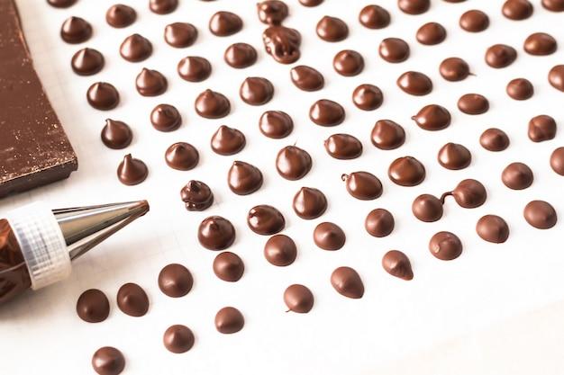 Concetto dell'alimento che produce le gocce di cioccolato casalinghe per il forno su fondo bianco