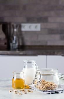 Concetto dell'alimento di prima colazione. granola fatta in casa, latte o, e miele sul tavolo tabckground in cucina