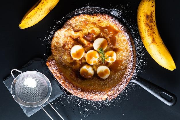 Concetto dell'alimento pancake olandese della guarnizione del caramello della banana del bambino casalingo in ghisa della padella sul nero