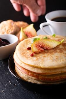 Concetto dell'alimento pila organica casalinga dei pancake con la prima colazione del fico sul nero