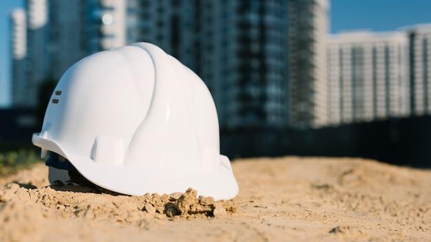 Concetto dell'architetto con il casco di sicurezza sulla sabbia