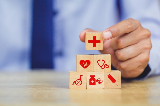 Concetto dell'assicurazione malattia, disposizione della mano che impila il blocco di legno con l'assistenza sanitaria dell'icona medica.