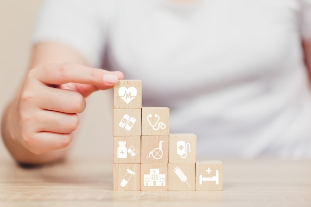 Concetto dell'assicurazione malattia, mano che organizza impilamento del blocco di legno con l'assistenza sanitaria dell'icona medica