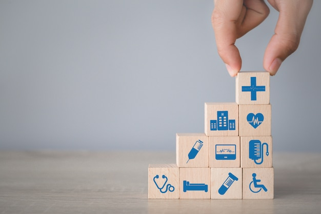 Concetto dell'assicurazione malattia, organizzazione della mano che impila il blocco di legno con l'assistenza sanitaria dell'icona medica.