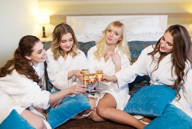 Concetto dell'hotel, di viaggio, di amicizia e di felicità - divertiresi sorridenti delle amiche.