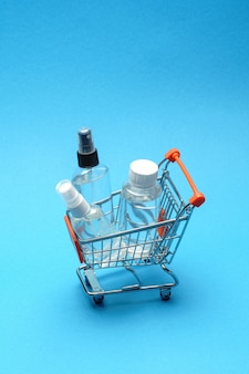 Concetto dell'igiene di protezione del virus della corona - liquido del prodotto disinfettante della mano dell'alcool nel carrello della spesa troplley su fondo blu. . lavare a mano nel cestino
