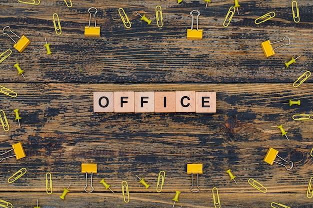 Concetto dell'ufficio con i cubi di legno, graffette, clip del raccoglitore sulla disposizione piana del fondo di legno.