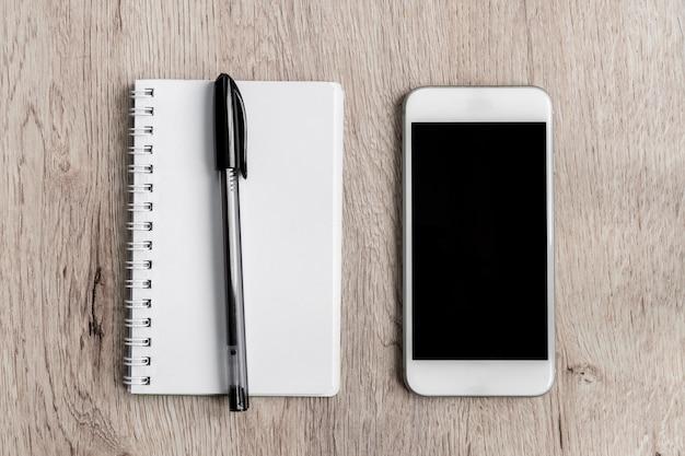 Concetto dell'ufficio e di affari - taccuino in bianco, smartphone e penna nera sulla tavola di legno. minima planarità, vista dall'alto.