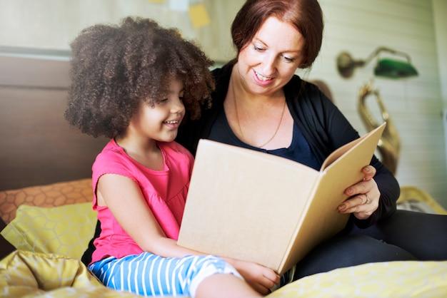 Concetto della camera da letto del libro di lettura della figlia della famiglia dei bambini