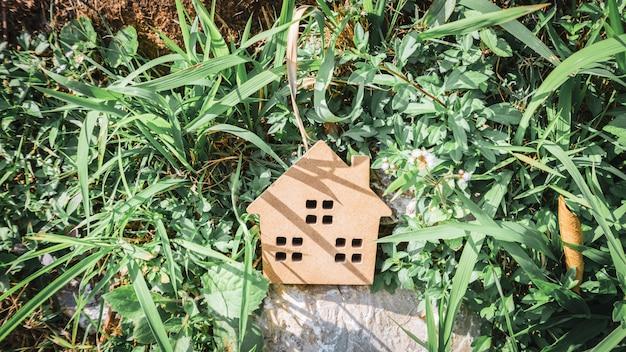 Concetto della casa di carta dura su erba verde.