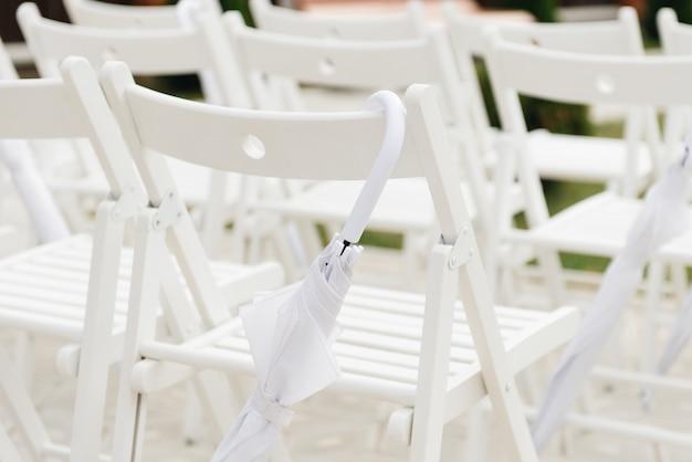 Concetto della decorazione di cerimonia di nozze, sedie di ricevimento nuziale ed ombrelli bianchi in caso di pioggia