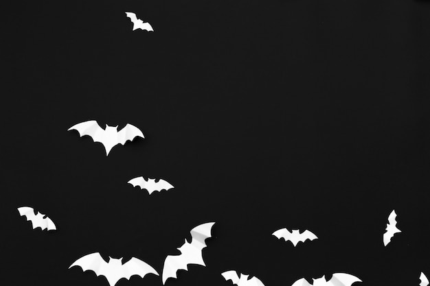 Concetto della decorazione e di halloween - pipistrelli di carta che volano fondo