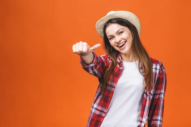 Concetto della gente, di gesto, di stile e di modo - giovane donna felice o ragazza teenager in abbigliamento casual che mostra i pollici su, isolato sopra fondo arancio.