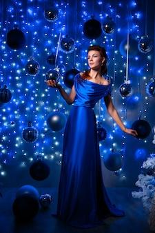 Concetto della gente, di stile, di feste, dell'acconciatura e di modo - giovane donna felice o ragazza teenager in vestito blu.