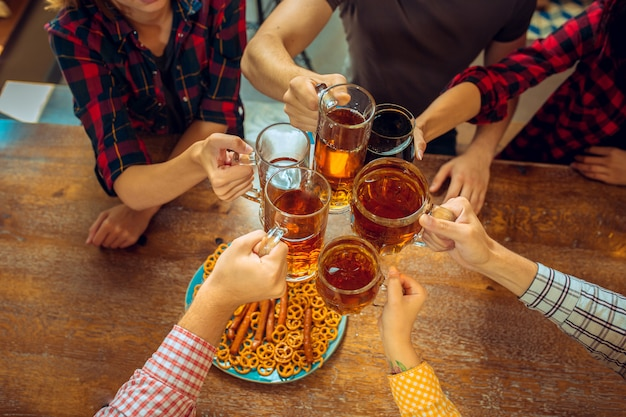 Concetto della gente, di svago, di amicizia e di comunicazione - amici felici che bevono birra, chiacchiere e tintinnio al bar o al pub