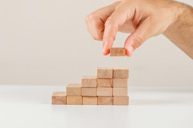 Concetto della gestione dei rischi e di affari sulla vista laterale del backgroud bianco. uomo d'affari ponendo blocco di legno sulla torre.