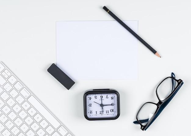 Concetto della gestione di tempo con l'orologio, la matita, la gomma, gli occhiali, la carta, tastiera sullo spazio bianco del fondo per testo, vista superiore. immagine orizzontale