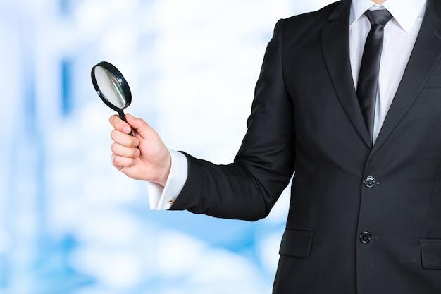 Concetto della lente d'ingrandimento della tenuta dell'uomo di affari