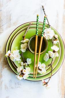 Concetto della primavera con la tazza del ramo di fioritura della pesca e del tè verde