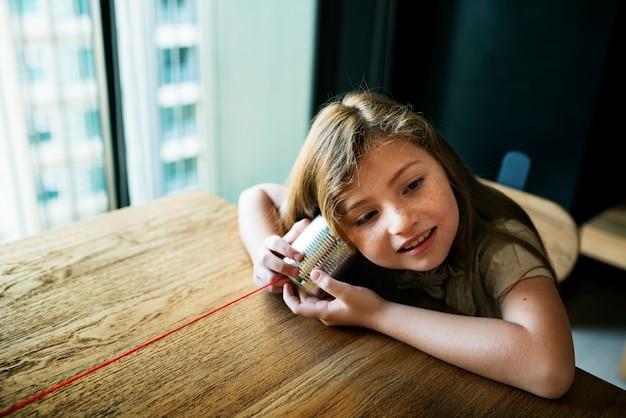 Concetto della ragazza del telefono del barattolo di latta