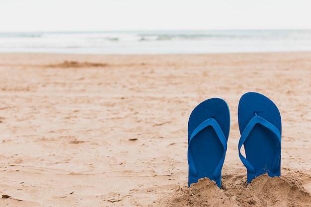 Concetto della spiaggia con le infradito in sabbia