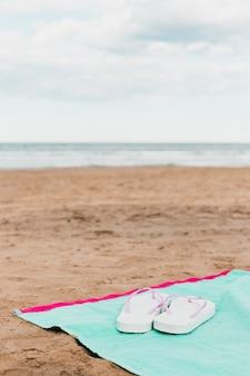 Concetto della spiaggia con le infradito sull'asciugamano