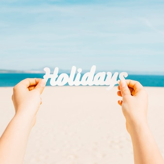 Concetto della spiaggia con le mani che tengono le lettere di feste
