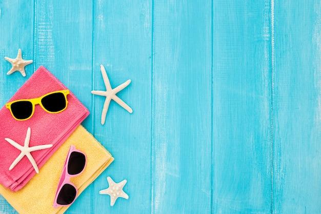 Concetto della spiaggia di vista superiore con l'asciugamano, i vetri e le stelle marine su fondo di legno blu