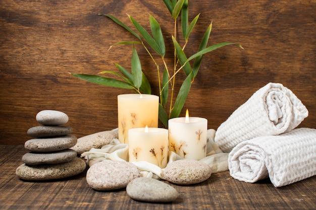 Concetto della stazione termale con le candele e gli asciugamani accesi