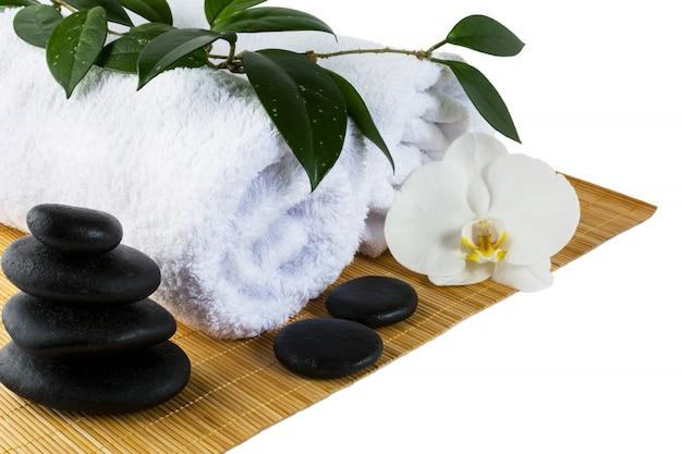 Concetto della stazione termale con le pietre bianche della stazione termale e dell'orchidea isolate su bianco