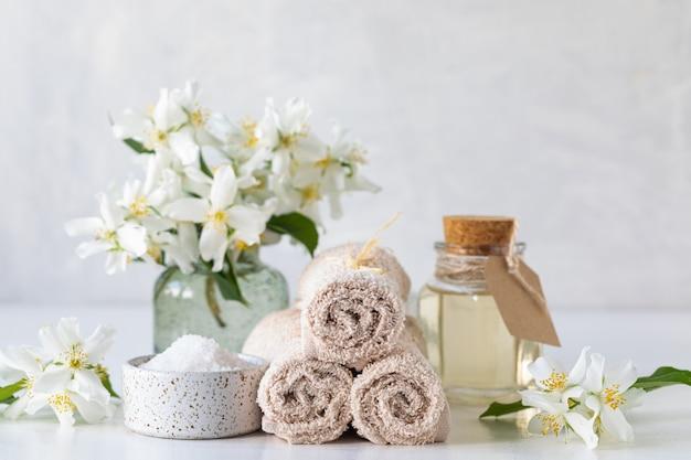 Concetto della stazione termale di olio di gelsomino, con sale da bagno e fiori
