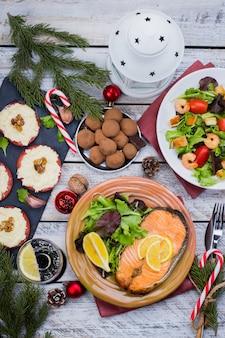 Concetto della tabella della regolazione della cena della famiglia del nuovo anno o di natale con la decorazione di festa. salmone, insalata, aperitivi e dessert deliziosi dell'arrosto di bistecca su di legno bianco. vista dall'alto