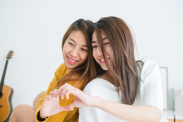 Concetto delle coppie lesbiche adorabili insieme. coppie delle giovani donne sorridenti che si siedono sul letto