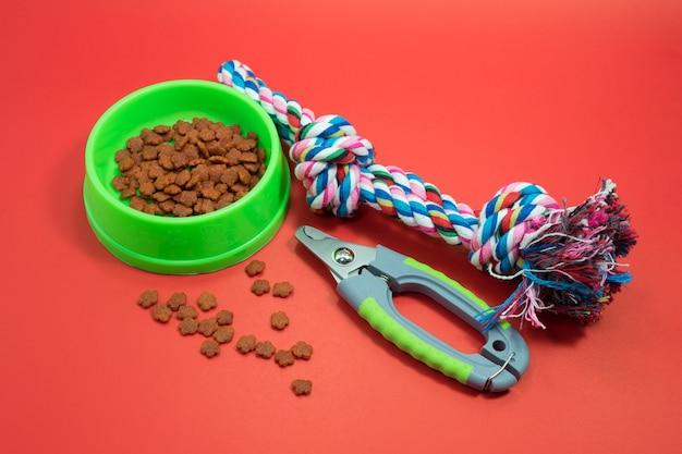 Concetto di accessori per animali domestici ciotole con cibo, forbicine per unghie e corda per mordere