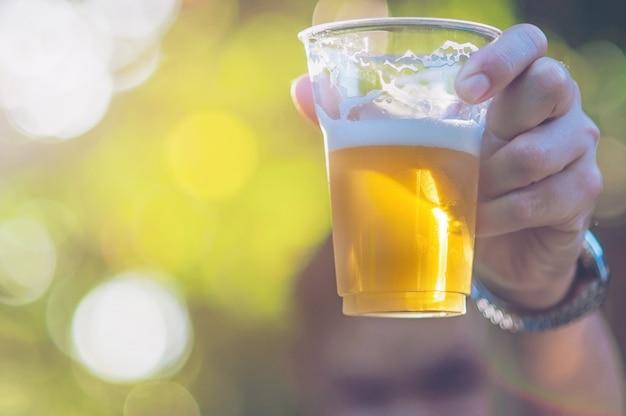 Concetto di acclamazioni della birra di celebrazione - mano alta vicina che sostiene i vetri di birra dell'uomo