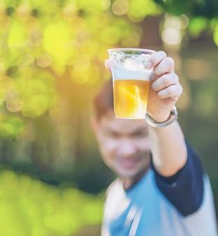 Concetto di acclamazioni della birra di celebrazione - mano alta vicina che sostiene i vetri di birra