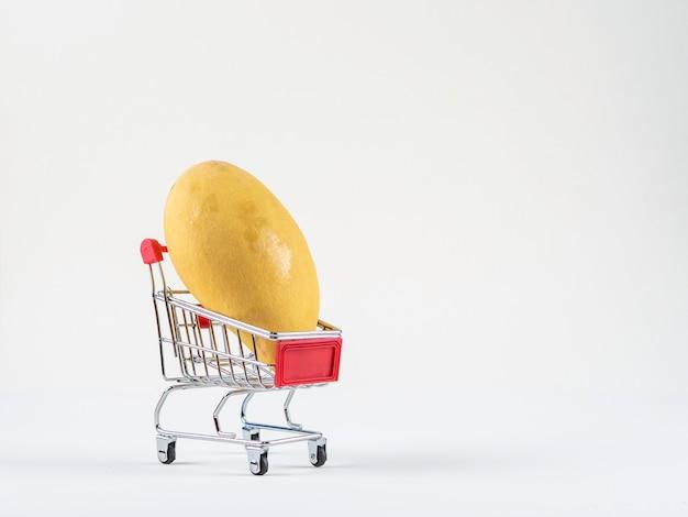 Concetto di acquisto dei manghi maturi con il carrello, canestro sui precedenti bianchi