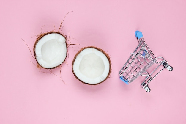 Concetto di acquisto di frutta. carrello della spesa, metà della noce di cocco rotta su uno sfondo rosa.