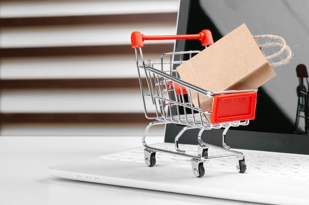 Concetto di acquisto online, carrello, computer portatile sullo scrittorio