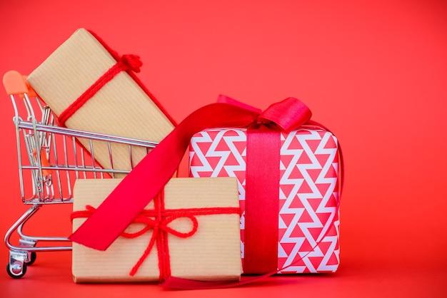 Concetto di acquisto online. carrello e contenitore di regalo su fondo rosso