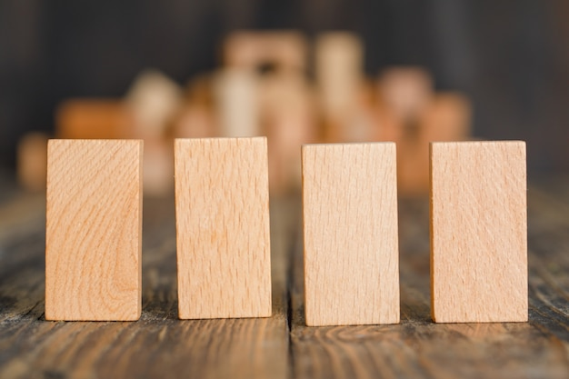 Concetto di affari con i blocchi di legno sulla vista laterale della tavola di legno.
