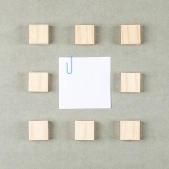 Concetto di affari con la nota appiccicosa tagliata, blocchi di legno sulla disposizione del piano di superficie grigia.