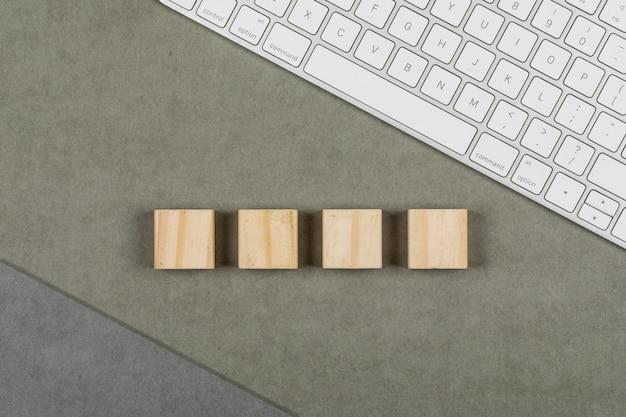 Concetto di affari con la tastiera, i cubi di legno sulla disposizione marrone e grigia grigia del piano del fondo.