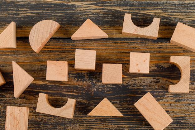 Concetto di affari con le forme geometriche di legno sulla disposizione piana del tavolo di legno.