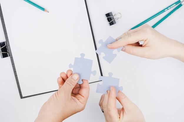 Concetto di affari con le mani che tengono i pezzi del puzzle