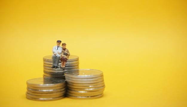 Concetto di affari. coppia di anziani seduti su una pila di monete d'argento.