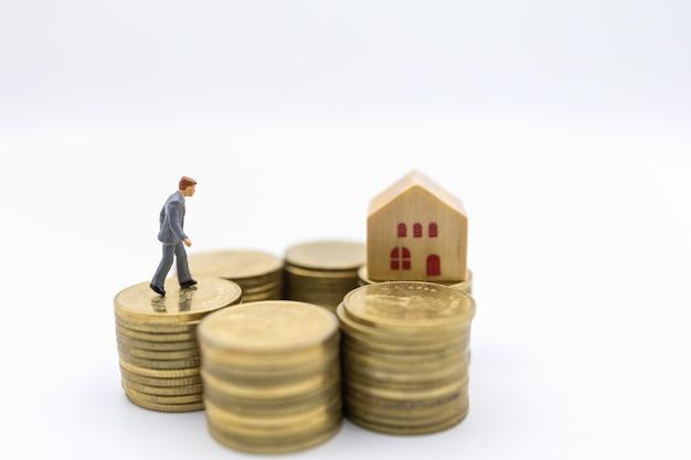 Concetto di affari, denaro, finanza, mutuo per la casa e gestione. chiuda su della figura miniatura dell'uomo d'affari che cammina sopra la pila di monete di oro al mini giocattolo di legno della casa