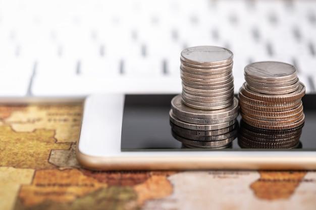Concetto di affari globali, denaro, finanza e tecnologia. chiuda su della pila di monete sul telefono cellulare astuto e sulla mappa di mondo con la tastiera di computer.